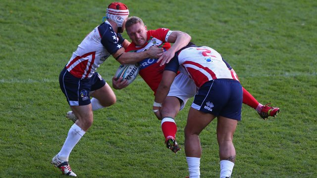 Christiaan Roets getting tackled by two USA players