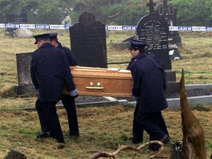 Irish police remove a coffin with the remains of Eamon Molloy from a cemetery in 1999