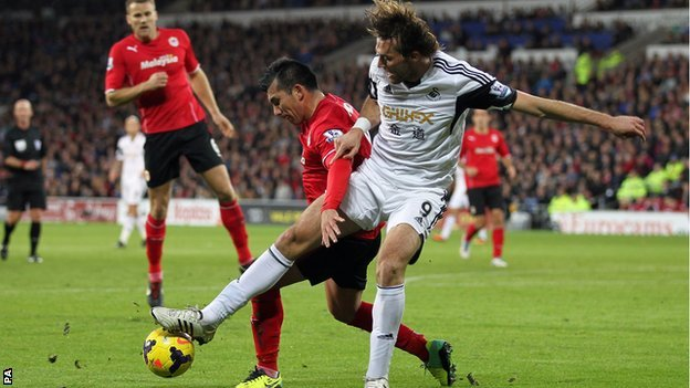 Swansea forward Michu battles with Cardiff midfielder Gary Medel
