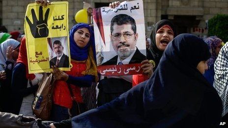 "Supporters of President Mohammed Morsi hold a poster of him with Arabic that reads, ""yes to legitimacy, Morsi is my president,"" right, and ""we support Rabaah with legitimacy,"" during a protest a day before the trial"