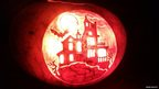 Pumpkin carved as a haunted house.