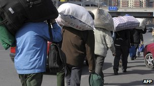 File photo: migrant workers carrying their luggage through a street in Beijing, 25 March 2009