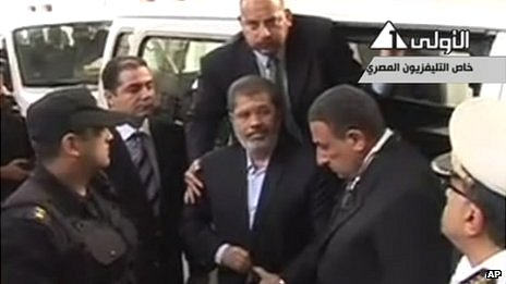 This image made from video broadcast on Egyptian state Television shows ousted President Mohammed Morsi arriving for a court hearing at a police academy compound in Cairo