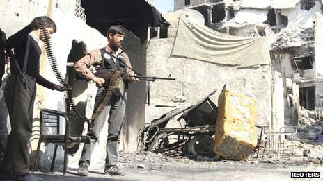 A Free Syrian Army fighter holds his machine gun as a fellow young fighter helps him to carry the ammunition in Old Aleppo, on 4 November 2013