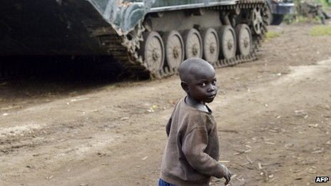 A young boy walks near a Democratic Republic of Congo army tank