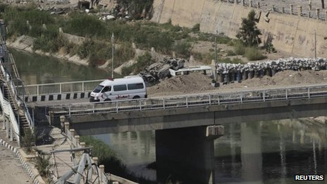 An ambulance crosses over a bridge where barricades and sandbags were piled as protection from snipers loyal to Syria's President Bashar al-Assad