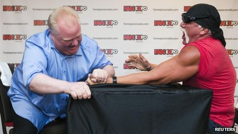 Toronto Mayor Rob Ford (L) arm wrestles former professional wrestler Hulk Hogan to mark the beginning of the Fan Expo in Toronto 23 August 2013
