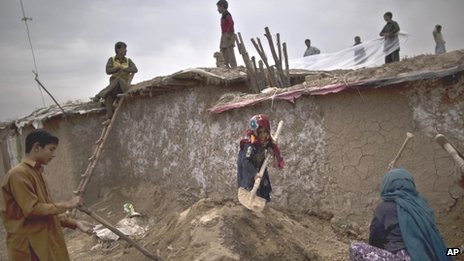 A Pakistani family, displaced from the tribal areas because of fighting between the Taliban and the army, fixes the rooftop of their mud house, in preparation for the rain season, in a poor neighbourhood on the outskirts of Islamabad (5 November 2013)