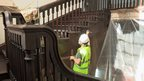 A carpenter at work staining the staircase
