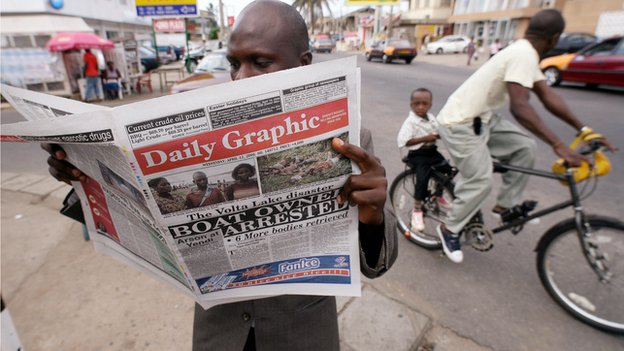 A man reads a newspaper in Accra on 12 April 2006