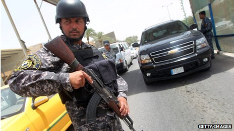 An Iraqi police officer, holding a weapon