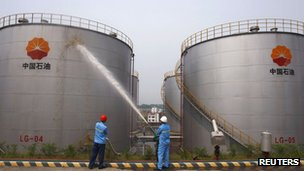 File photo: employees spray water to cool down oil tanks at a storage facility, which belongs to one of China's biggest state-owned firms PetroChina oil, in Suijing, Sichuan Province, 13 August 2010