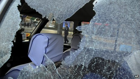 A Chinese police officer is framed by the glass window of a vehicle damaged by explosions outside the provincial headquarters of China's ruling Communist Party in Taiyuan in north China's Shanxi province, 6 November 2013