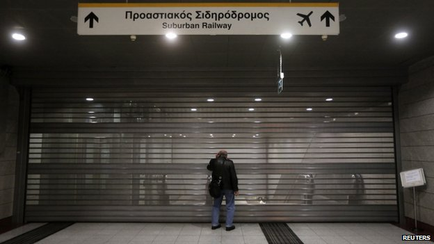 A man stands at a shutter at a railway station in Athens, 6 November