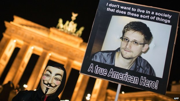 Anonymous supporters hold up a poster of Edward Snowden in Berlin, 5 November