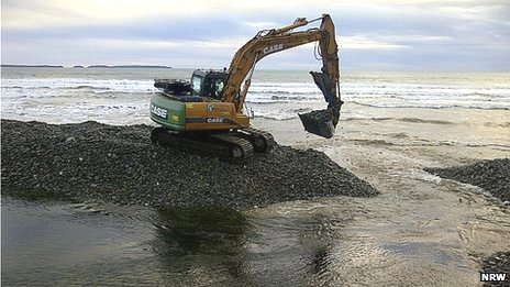 Digger working to remove sand and shale on Pembrokeshire beach