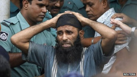 Prisoner reacts as police force him into a van after the verdict for a 2009 mutiny is announced, in Dhaka, 5 November 2013