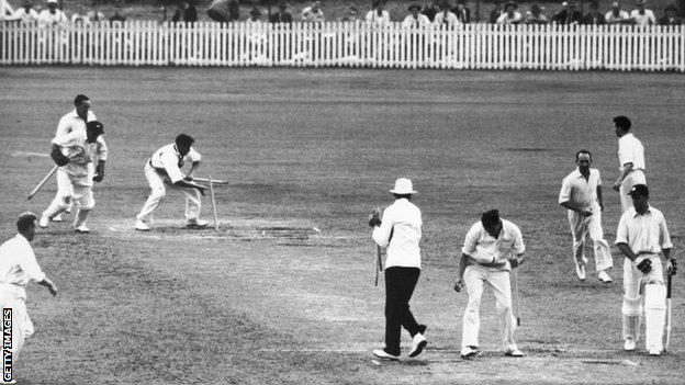 Wicketkeeper Don Tallon gathers up the stumps after Australia win