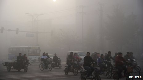 Residents ride bicycles along a street amid heavy haze in Xingtai, Hebei province, on 3 November 2013