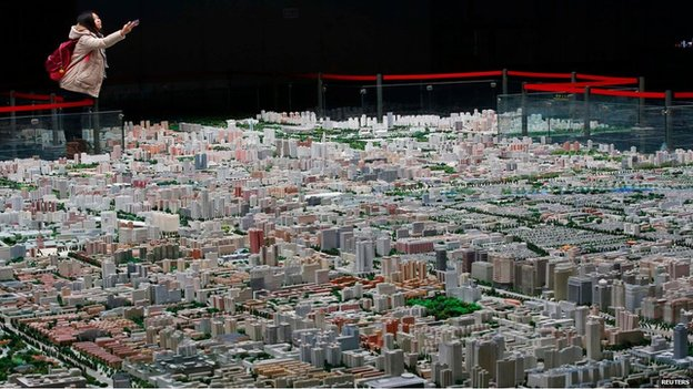 Visitor to the Beijing Planning Exhibition takes a picture of the scale model of Beijing's downtowns (5 November)