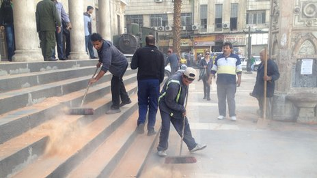 Men sweeping away the debris after mortar attack on the Hijaz railway station