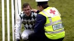 Jockey AP McCoy is attended to by a medic after a fall