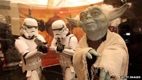 Stormtroopers from the Star Wars series of films looking at a model of Yoda