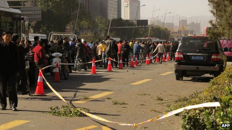 People stand on a street after an explosion outside a provincial headquarters of China's ruling Communist Party in Taiyuan, north China's Shanxi province on 6 November 2013