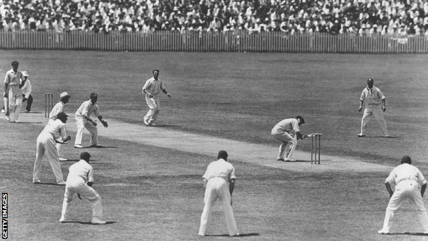 """Australia captain Bill Woodfull ducks a short delivery from Harold Larwood with a """"Bodyline"""" field in place"""