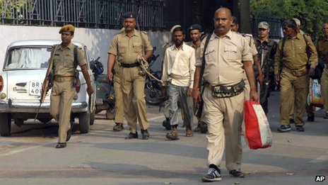 An Indian policeman holds a rope tied to a man, (centre) one of the accused arrested in connection with the 27 October bomb blasts