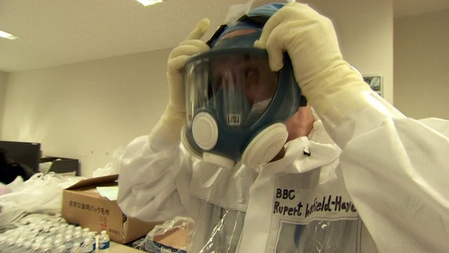 The BBC's Japan correspondent, Rupert Wingfield-Hayes, puts on a protective face mask as he prepares to go into the Fukushima nuclear plant