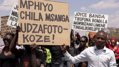 Protesters in Malawi hold up placards wishing Malawi's Budget Director Paul Mphwiyo a quick recovery, so that he can come home soon from South Africa where he is receiving treatment following his attempted assassination - October 2013
