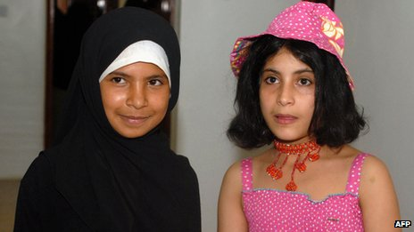 Yemeni child brides, eight year-old Nojud Ali (L) and nine year-old Arwa (R), pose for a picture as they celebrate their divorces, granted them by a Yemeni court, with a party in the capital Sanaa (30 July 2008)