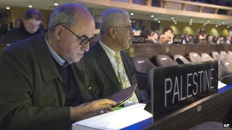 The Palestinian Ambassador to UNESCO Elias Sanbar, left, checks his tablet during a session of the UNESCO General Conference, in Paris, Friday 8 November 2013