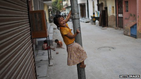 Indian street child climbing lamppost