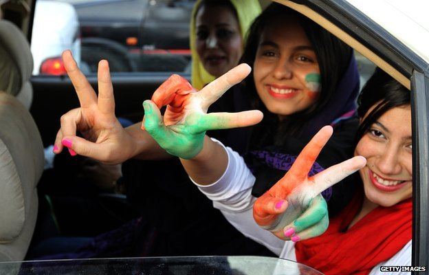 Three Iranian women football supporters in a car with their hands and faces painted in the colours of Iran's flag