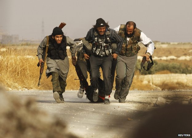 Rebel fighters carry the body of a dead comrade near Base 80, Aleppo,  Syria, 8 November