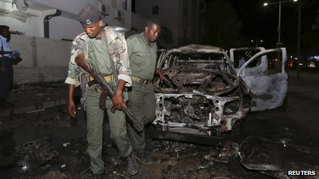 Somali policemen inspect the scene of an explosion outside the Maka Al-Mukarama hotel in Somalia's capital Mogadishu (8 November 2013)