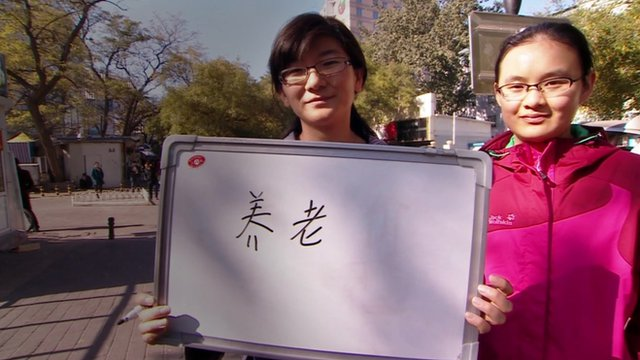 A woman holds up a white board