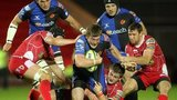 Scarlets' Richard Kelly, Craig Price and Adam Warren tackle Hugh Gustafson of Newport Gwent Dragons