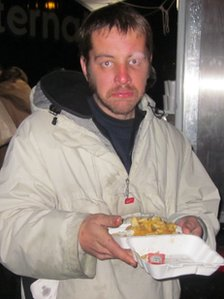 Homeless man eating donated fish and chips