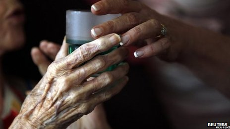 Nurse gives elderly woman a drink