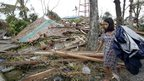Girl searches for salvageable materials among debris in Tacloban. 9 Nov 2013