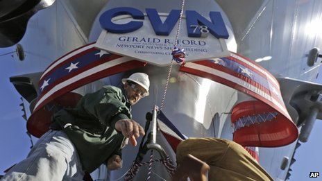 Shipbuilding workers Stephen Gilliland, left, and John Gies, right, prepare the for the christening of the Navy's newest nuclear powered aircraft carrier USS Gerald R Ford at the shipyard in Newport News, Va., Friday, Nov. 8, 2013