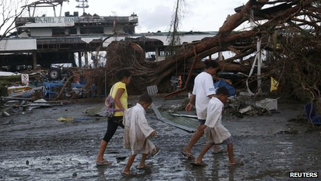 Survivors walk past a fallen tree outside an airport after super Typhoon Haiyan battered Tacloban city