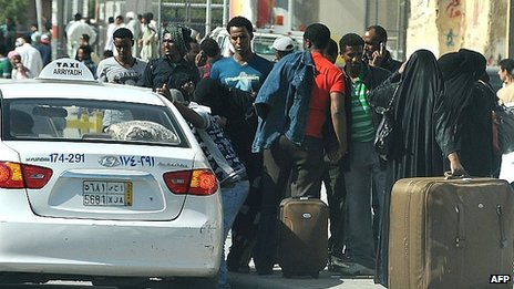 Foreign workers wait for a taxi as they leave the Manfuhah neighbourhood of Riyadh. 10 Nov 2013