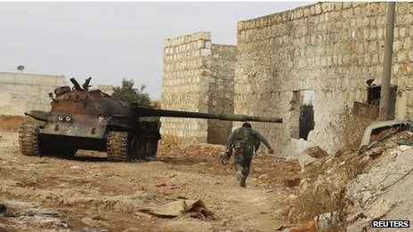 A fighter from Tawhid Brigade, which operates under the Free Syrian Army, runs beside a tank in Base 80 area of Aleppo, Syria, 30 November