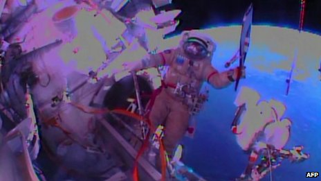 Cosmonaut Oleg Kotov holds the Sochi 2014 Winter Olympic Games Torch during a spacewalk outside the International Space Station on November 9, 2013