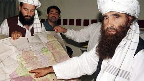 Jalaluddin Haqqani (right), points to a map of Afghanistan while serving as a Taliban minister. File photo taken in Islamabad on 19 October 2001.