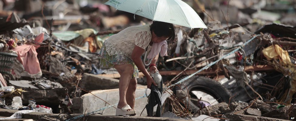 Woman sorts through belongings in Tacloban